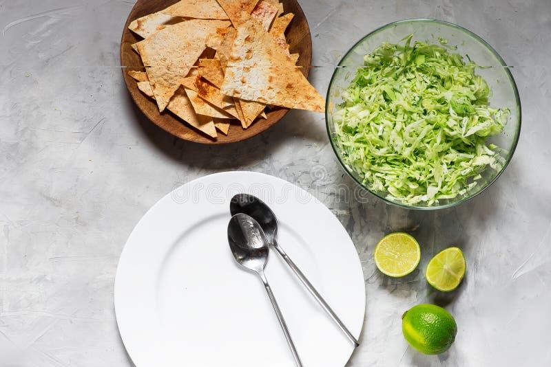 Witte plaat met soeplepels, spaanders en salade van verse kool met greens stock afbeelding