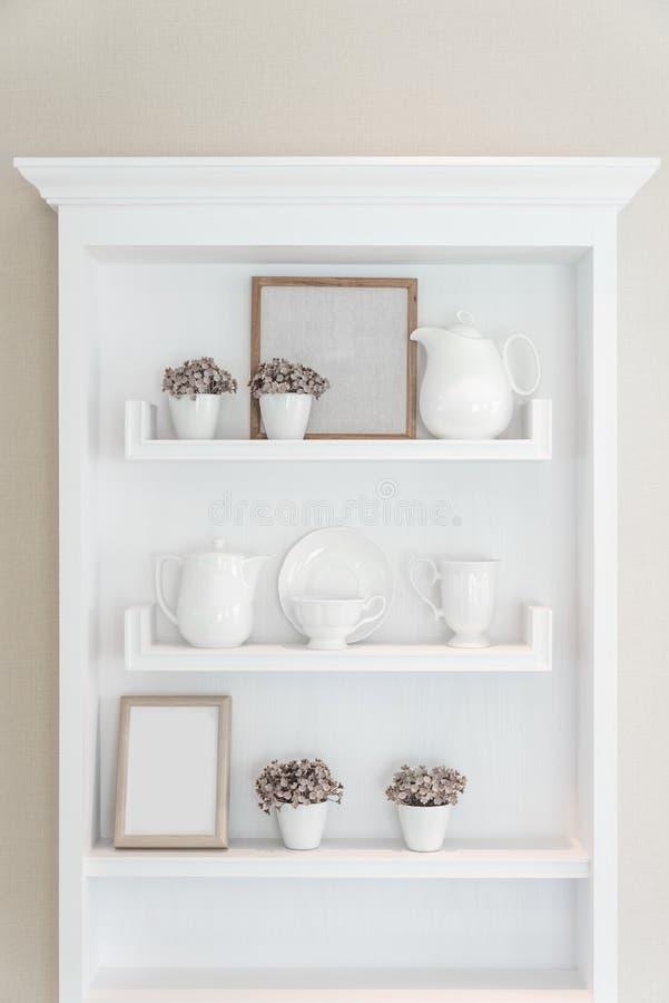 Witte plank met uitstekend porseleinvaatwerk binnenshuis stock afbeelding