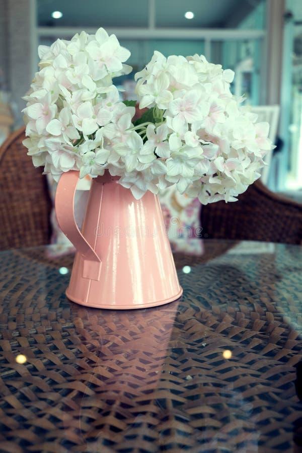 Witte plastic bloemen in roze bloemvaas op het rotanweefsel stock afbeeldingen