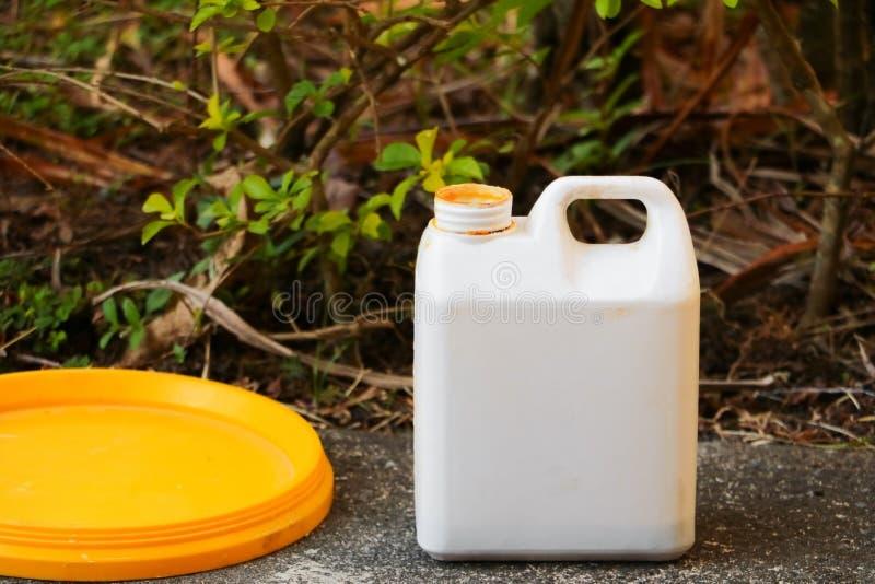 Witte plastic gallon olie voor kleurencombinaties op de cementvloer stock foto
