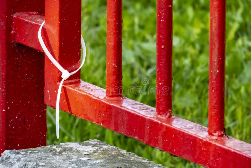 Witte plastic handcuffs en de rode omheining van het tuinijzer stock foto's