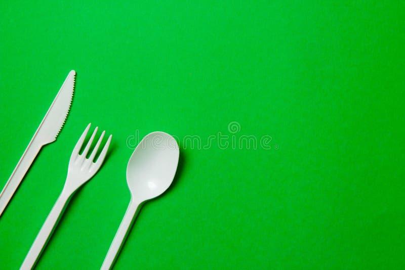 Witte plastic messen voor ??nmalig gebruik, lepels, vorken op een groene achtergrond Zeg nr aan plastiek voor ??nmalig gebruik Mi stock fotografie