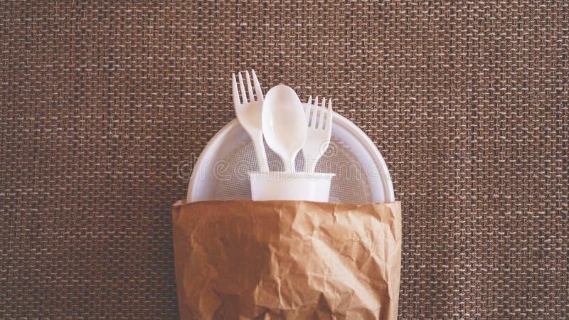 Witte plastic schotels in een document pakket op beige achtergrond stock afbeelding