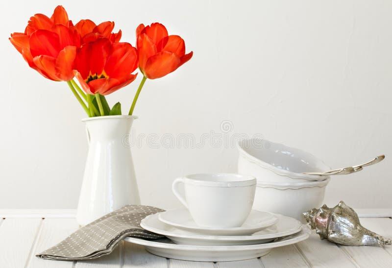 Witte platen, kommen, messenmaker en tulpen stock foto