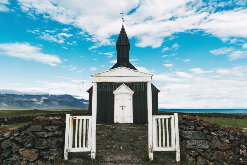 witte poorten en steenmuur bij het binnengaan aan kleine kerk in Budir, Snaefellsnes royalty-vrije stock afbeelding