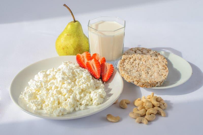 Witte porseleinplaat met kaas en rijpe aardbeien, cachou en transparante glaskop met melk groene peren en crackers royalty-vrije stock foto