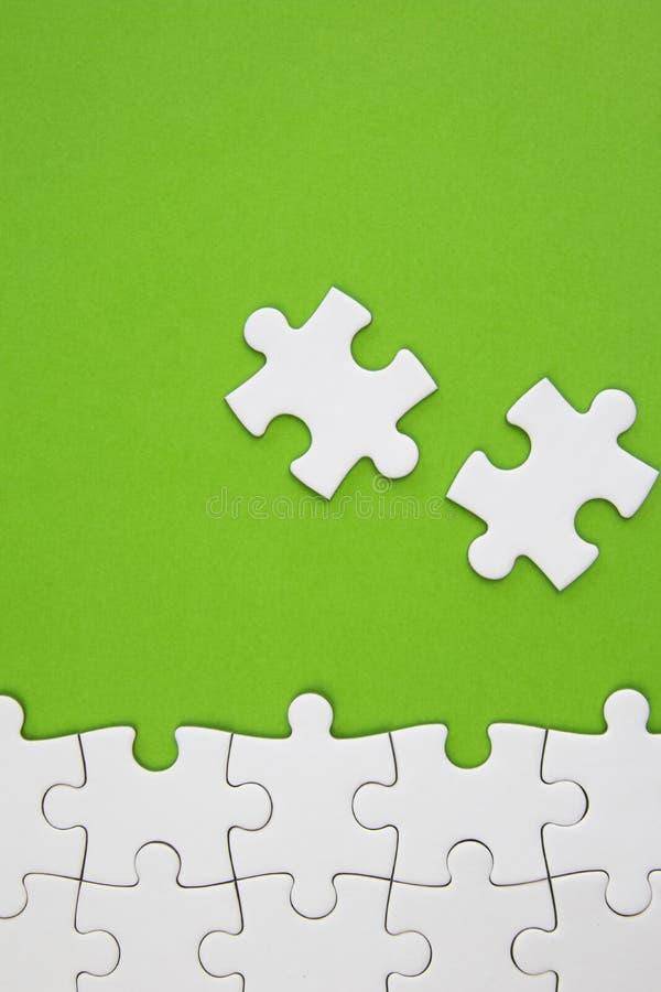 Witte puzzelstukken op groene achtergrond met negatieve ruimte stock foto
