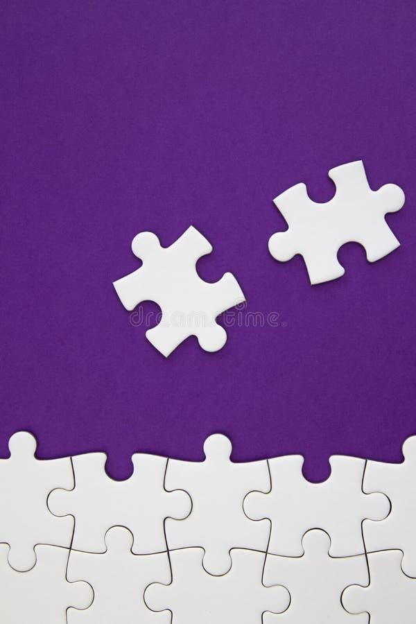 Witte puzzelstukken op purpere achtergrond met negatieve ruimte stock afbeeldingen