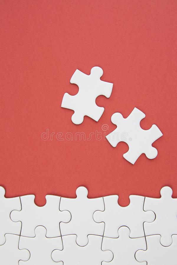 Witte puzzelstukken op rode achtergrond met negatieve ruimte royalty-vrije stock afbeeldingen