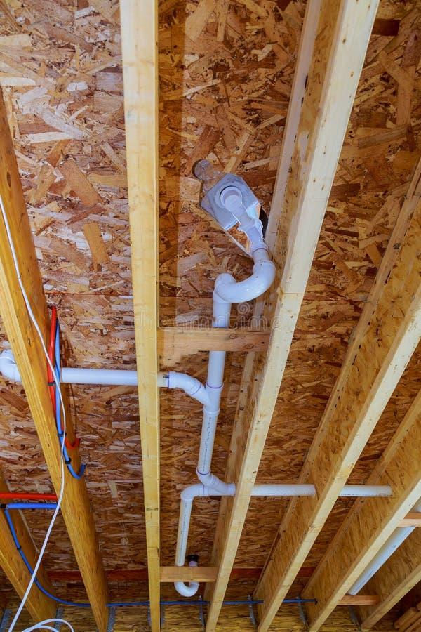 Witte PVS-pijpleiding onder wit plafond in het nieuwe gebouw bouwnijverheidspijpleiding voor drainagesysteem stock foto's