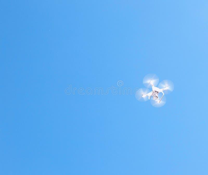 Witte quadcopter neemt foto's en schiet video in de hemel, exemplaarruimte, hommel stock afbeeldingen