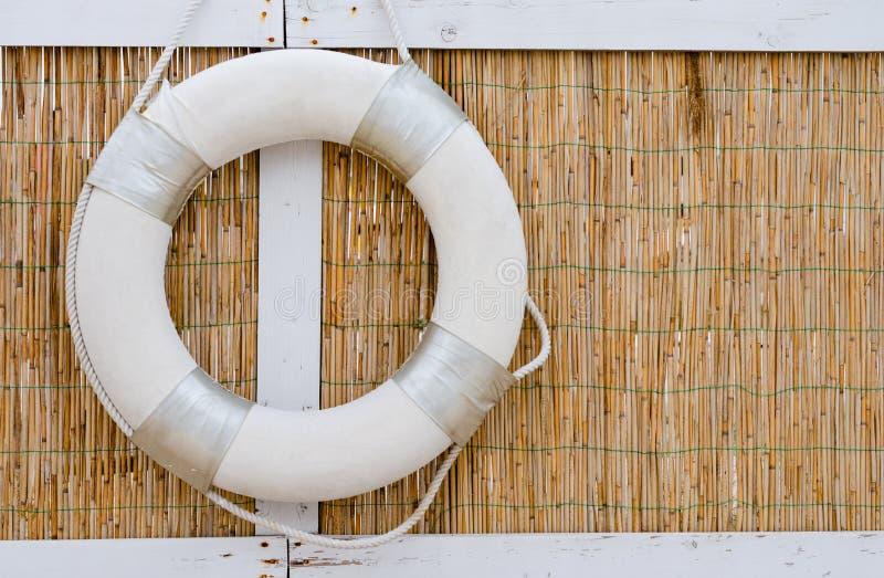 Witte reddingsboten die op een rietmuur bij de kust hangen royalty-vrije stock fotografie