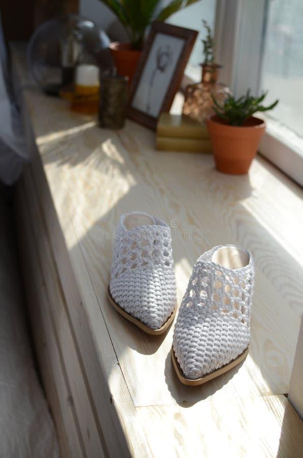 Witte rieten pantoffels op de venstervensterbank, bloempot met bloem, fotokader stock afbeeldingen