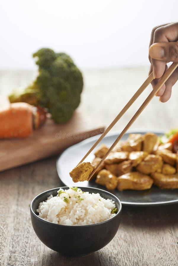 Witte rijst met kerrie en kip in zwarte plaat op houten lijst stock foto's