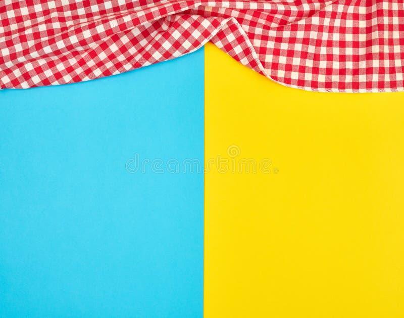 witte rode geruite keukenhanddoek op een blauwe gele achtergrond royalty-vrije stock afbeeldingen