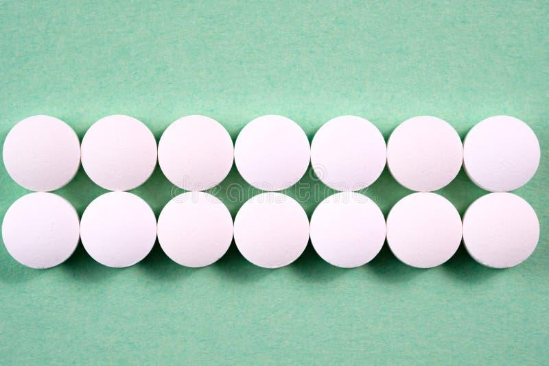 Witte ronde farmaceutische pillen op groene achtergrond royalty-vrije stock afbeelding