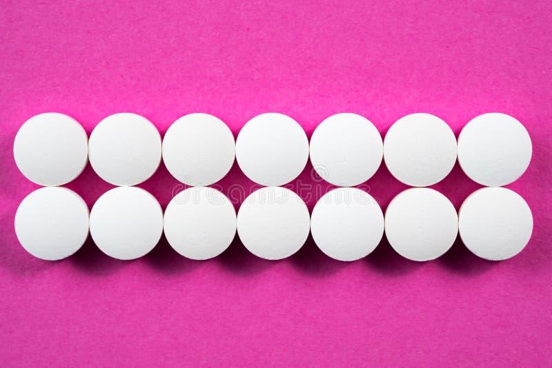 Witte ronde farmaceutische pillen op roze achtergrond stock afbeelding