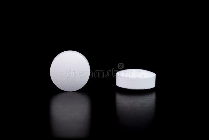 Witte ronde farmaceutische pillen op weerspiegelende oppervlakte, zwarte achtergrond royalty-vrije stock afbeelding