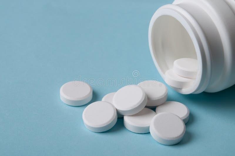 Witte ronde pillen die uit de geneeskundefles morsen stock fotografie