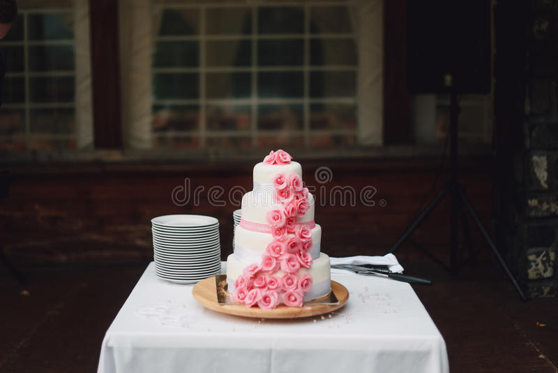 Witte roze huwelijkscake met rozen op bureau stock foto's