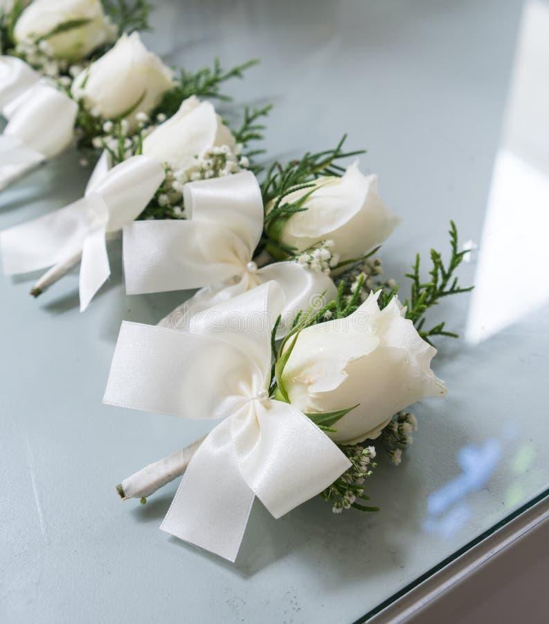 Witte rozen boutonniere met witte groomsmen van het vlinderdaslint op g stock foto
