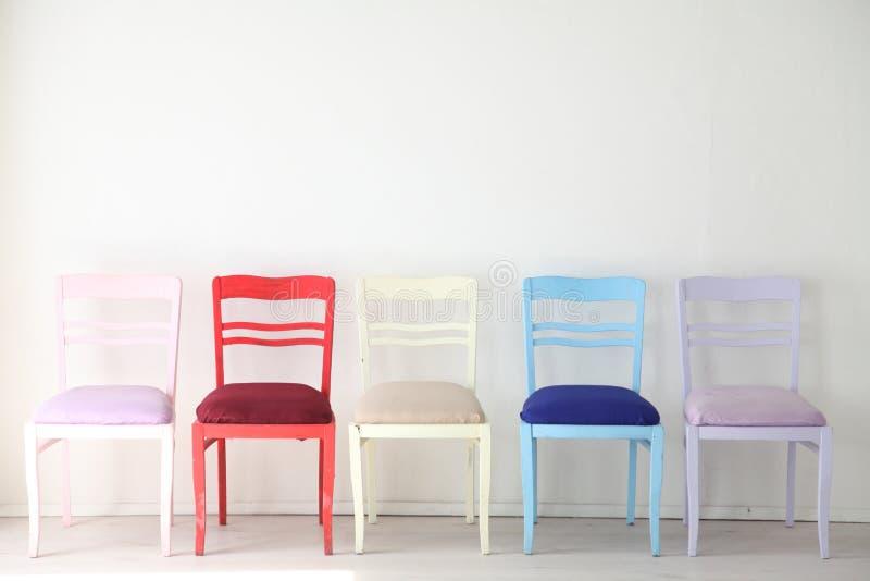 Witte ruimte met kleurrijke stoelen blauwe gele rode blauwe purple royalty-vrije stock fotografie