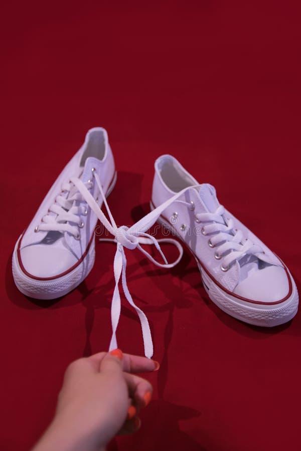Witte schoenen met geknoopt kant op een rode achtergrond royalty-vrije stock foto's