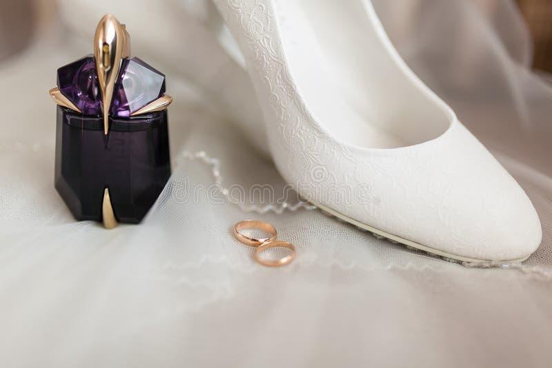 Witte schoenen, parfum, trouwringen op een lichte achtergrond royalty-vrije stock foto's