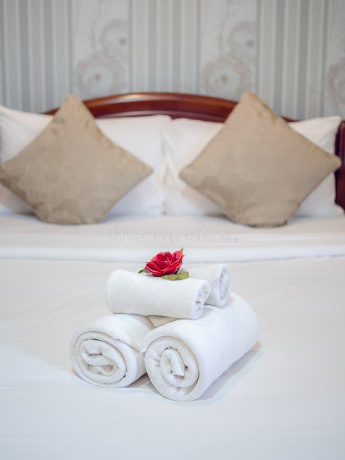 Witte schone handdoekendecoratie met rode bloem op wit schoon bed in hotelruimte stock fotografie