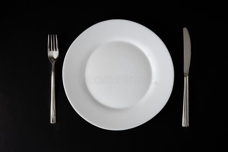 Witte schone plaat en roestvrije mes en vork die op zwarte achtergrond wordt ge?soleerd Hoogste mening royalty-vrije stock afbeelding