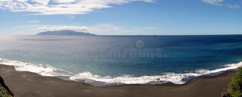 Witte schuimende Romaanse golven het zwarte zandstrand stock afbeeldingen
