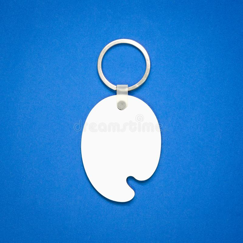 Witte sleutelring op blauwe achtergrond Zeer belangrijke ketting voor uw ontwerp Hangende toebehoren of herinnering De vorm van h stock afbeelding