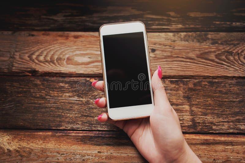Witte smartphone in vrouwelijke handen op een houten achtergrond stock foto