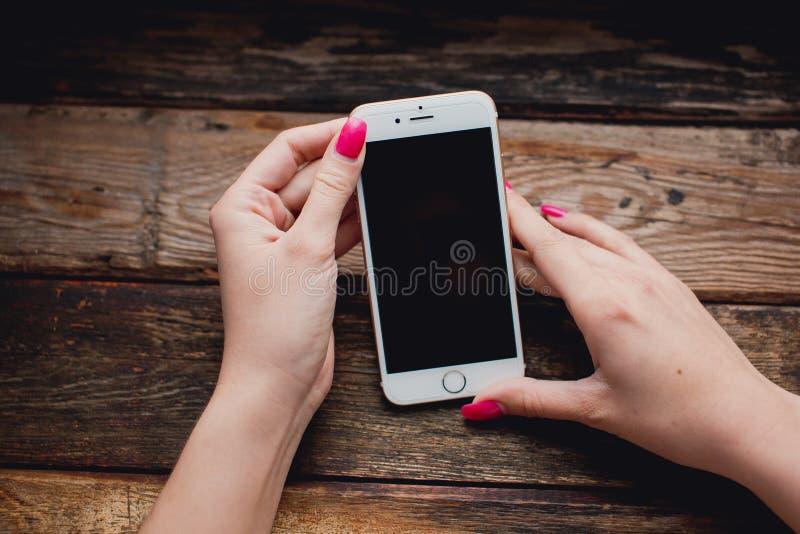 Witte smartphone in vrouwelijke handen op een houten achtergrond stock afbeelding