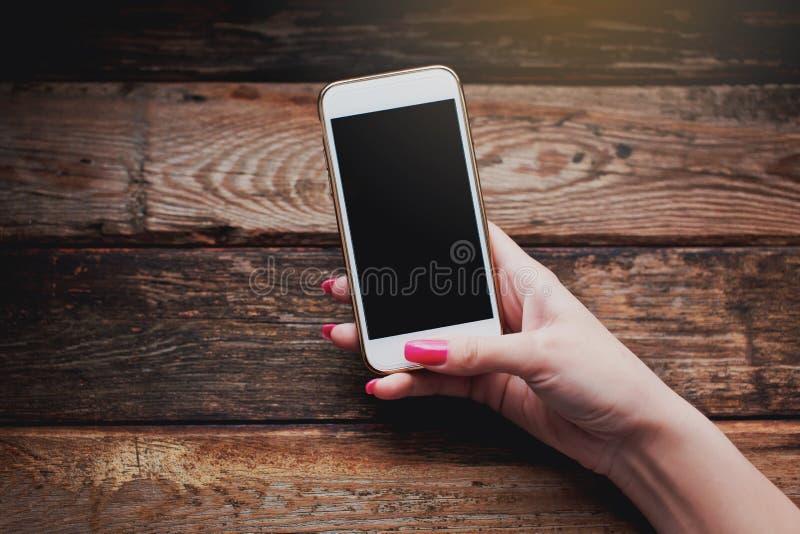 Witte smartphone in vrouwelijke handen op een houten achtergrond royalty-vrije stock foto