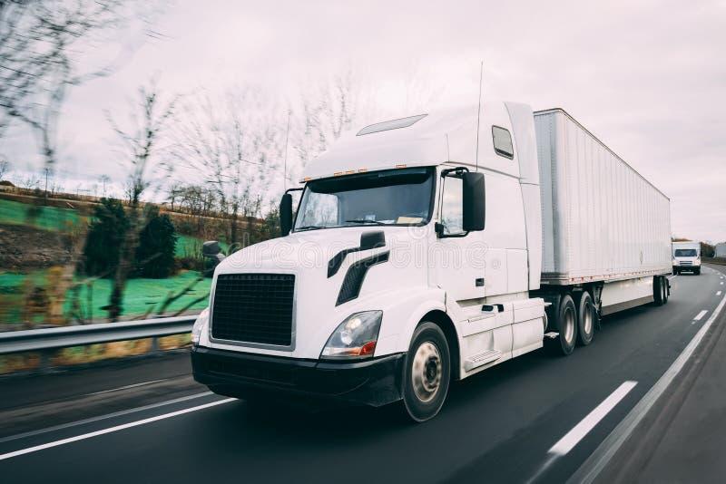 Witte 18 speculant semi-vrachtwagen op weg met motieonduidelijk beeld stock fotografie