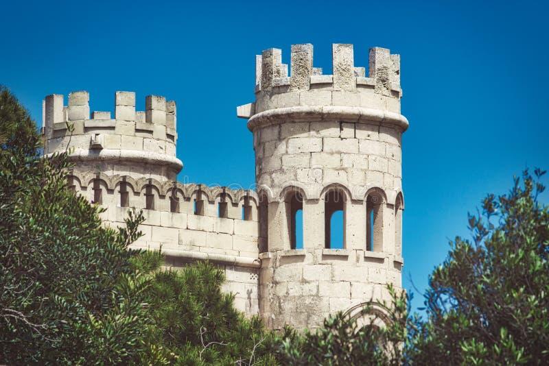 Witte steentorentjes van een middeleeuws kasteel tegen een blauwe hemelachtergrond stock foto's