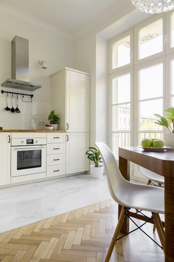 Witte stoel bij houten eettafel in eenvoudige keuken binnenlandse wi stock afbeelding