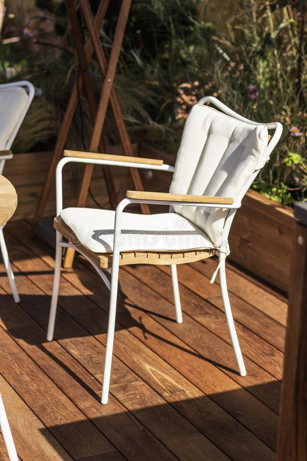 Witte stoel, modern ontwerp op een houten terras Zon, rust en eenzaamheid met zich stock afbeelding