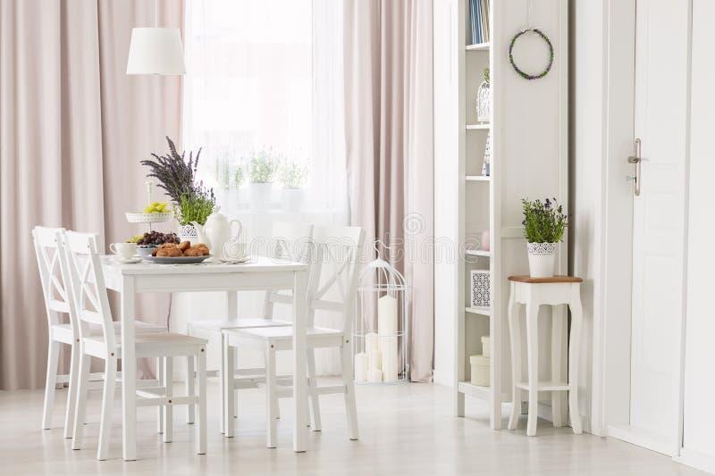 Witte stoelen bij eettafel met installaties in modern vlak binnenland met roze gordijn en venster Echte foto royalty-vrije stock afbeeldingen