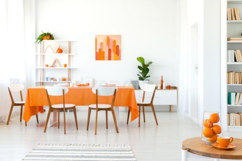 Witte stoelen bij lijst met oranje doek in modern eetkamerbinnenland met installatie en affiche royalty-vrije stock fotografie