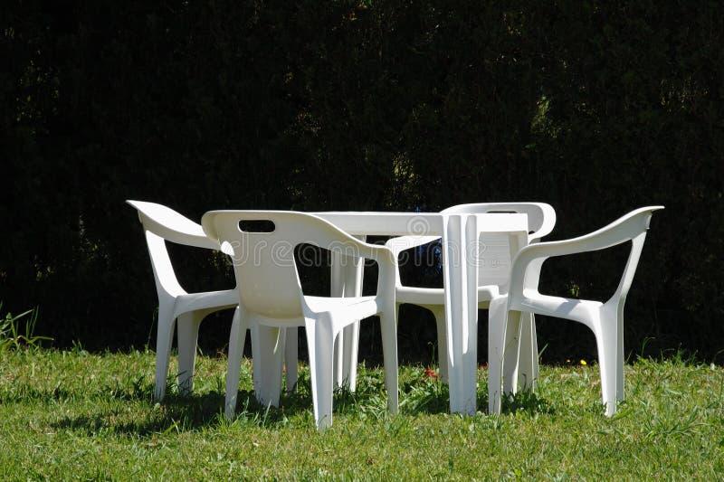 Witte stoelen en lijst in gazon royalty-vrije stock fotografie