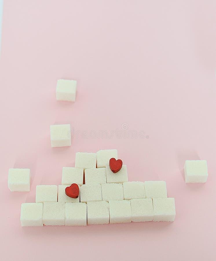 Witte suikerkubussen op een roze achtergrond Wat de concepten diabetes en calorie-inname het concept hartkwaal zijn Nr royalty-vrije stock foto