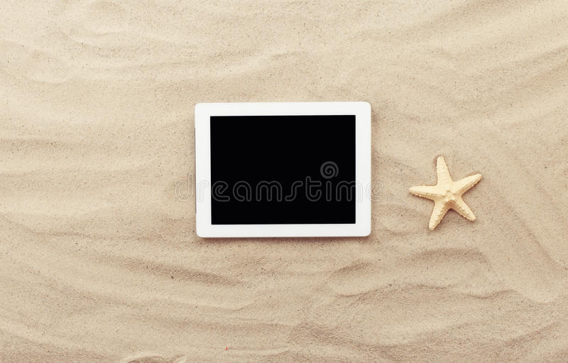 Witte tablet met het lege scherm op het zand stock foto's