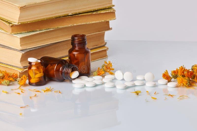 Witte tabletten en pillen met goudsbloem Calendula en oude boeken op witte spiegelachtergrond royalty-vrije stock foto's