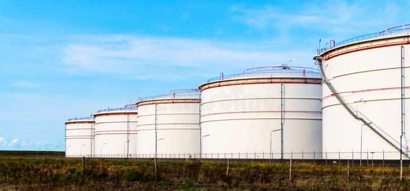 Witte tanks in tanklandbouwbedrijf met blauwe hemel stock afbeelding