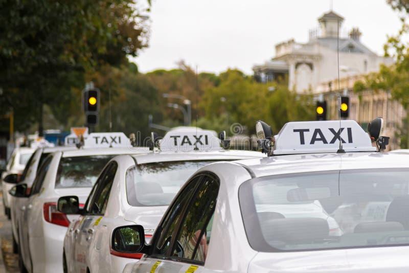 Witte taxiauto's die langs het voetpad in Adelaide, Australi parkeren royalty-vrije stock foto's