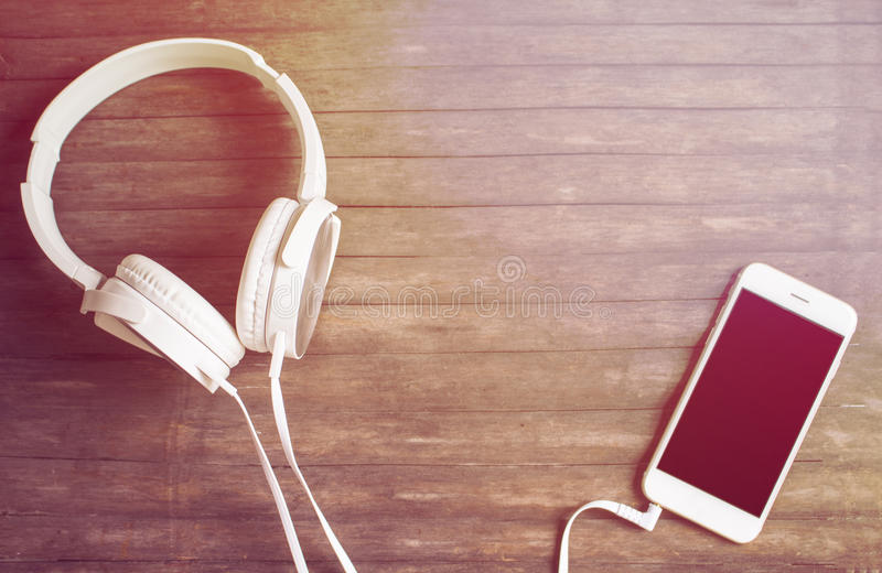 Witte telefoon en hoofdtelefoons op houten lijst Warme gele gestemde foto royalty-vrije stock foto