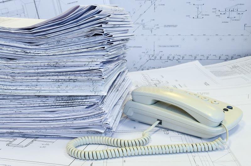 Witte telefoon en hoop van gevormde projecttekeningen stock afbeelding