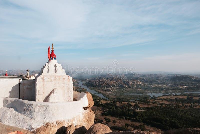 Witte tempel op de grote heuvel tegen de vallei met rivier, hemel en bergen in hampidorp van India stock foto's